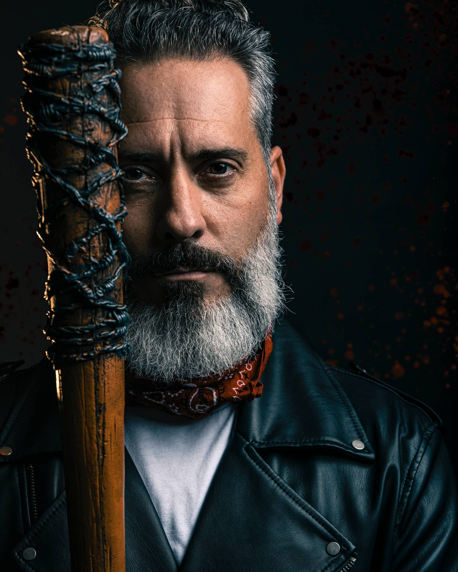 In this styled tribute photograph by Alexander Worth of Jawfox Photography, a man cosplays Negan from The Walking Dead, wearing a leather jacket and carrying the villain's barbed wire-wrapped bat, Lucille.