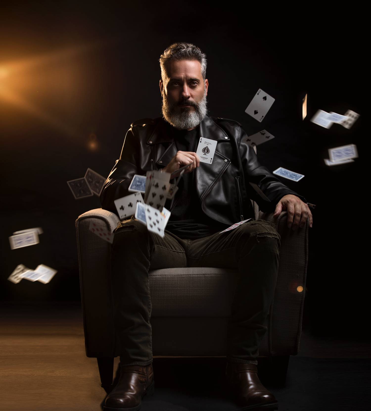 In this styled tribute photograph by Alexander Worth of Jawfox Photography, a man cosplays Negan from The Walking Dead, wearing Alton Brown clothing and seated in a leather chair as playing cards fall down around him.