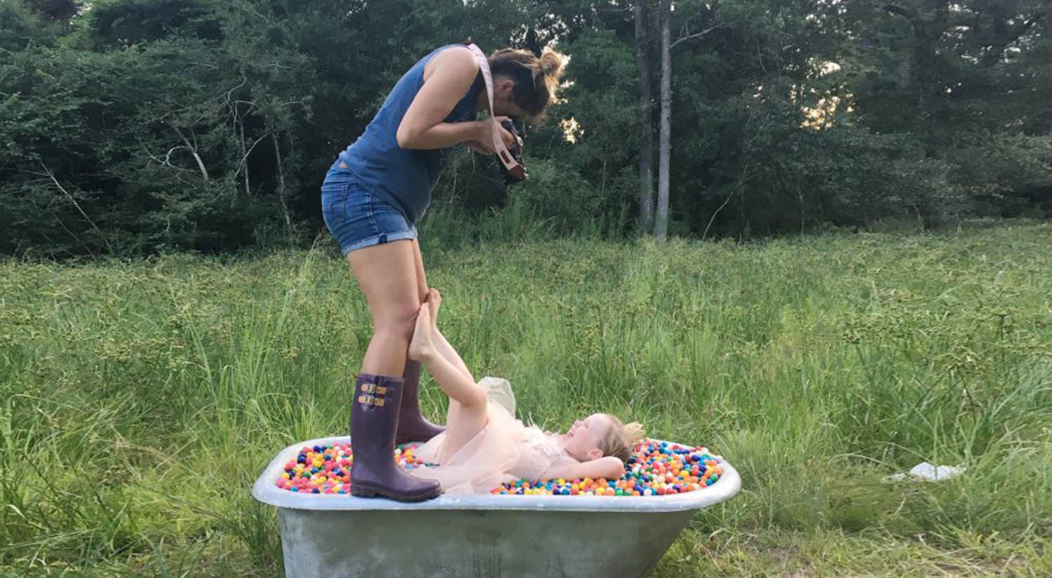 Photographer Shalonda Chaddock stands over a clawfoot tub during an outdoor photo shoot with a young child