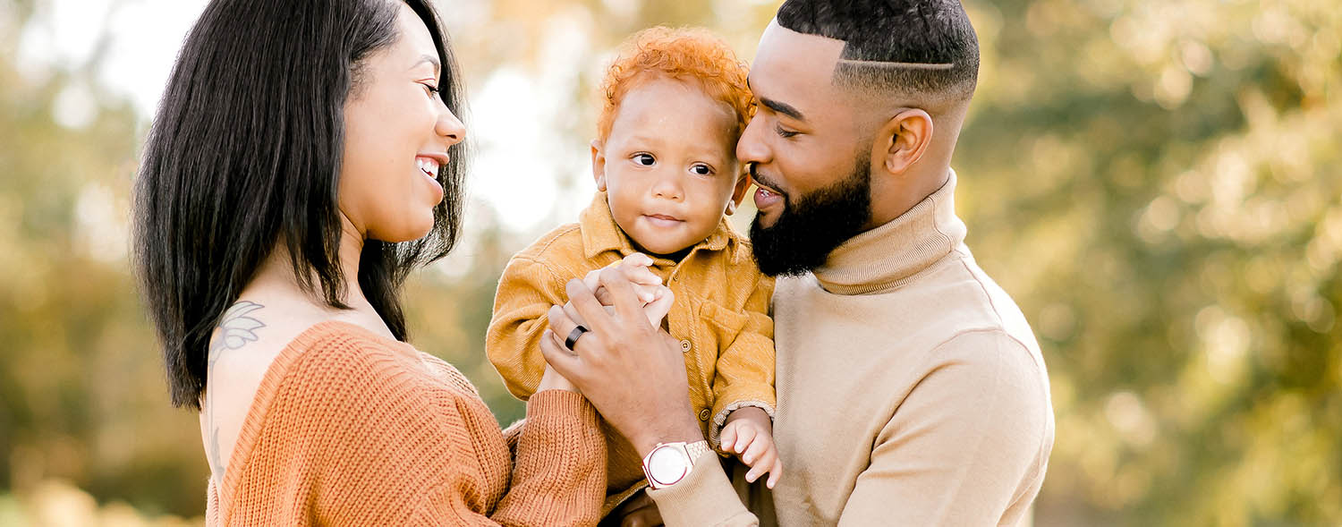 A mom, dad, and toddler son snuggle close together in a vibrant outdoor portrait