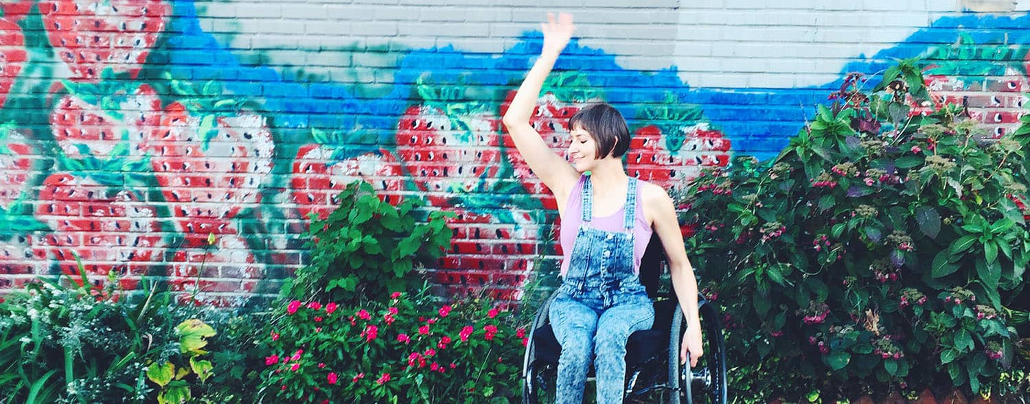 Writer Rebekah Taussig dances joyfully in front of a floral mural while sitting in her wheelchair