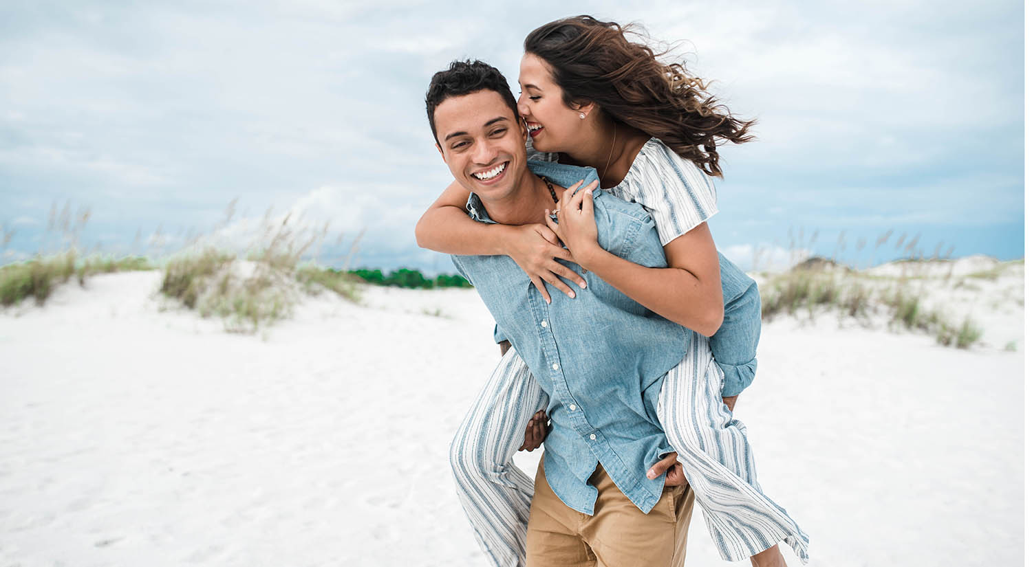 A woman laughs will her husband gives her a piggy-back ride at the beach
