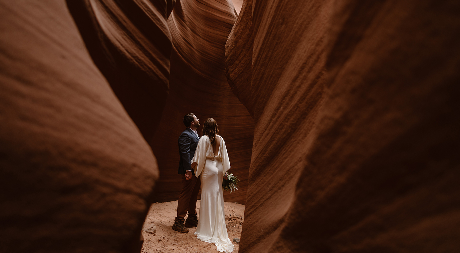 A bride and groom stand in a red rock canyon