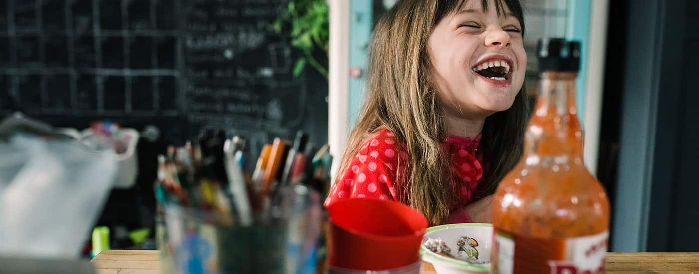 a little girl in a red shirt sits at a kitchen counter laughing