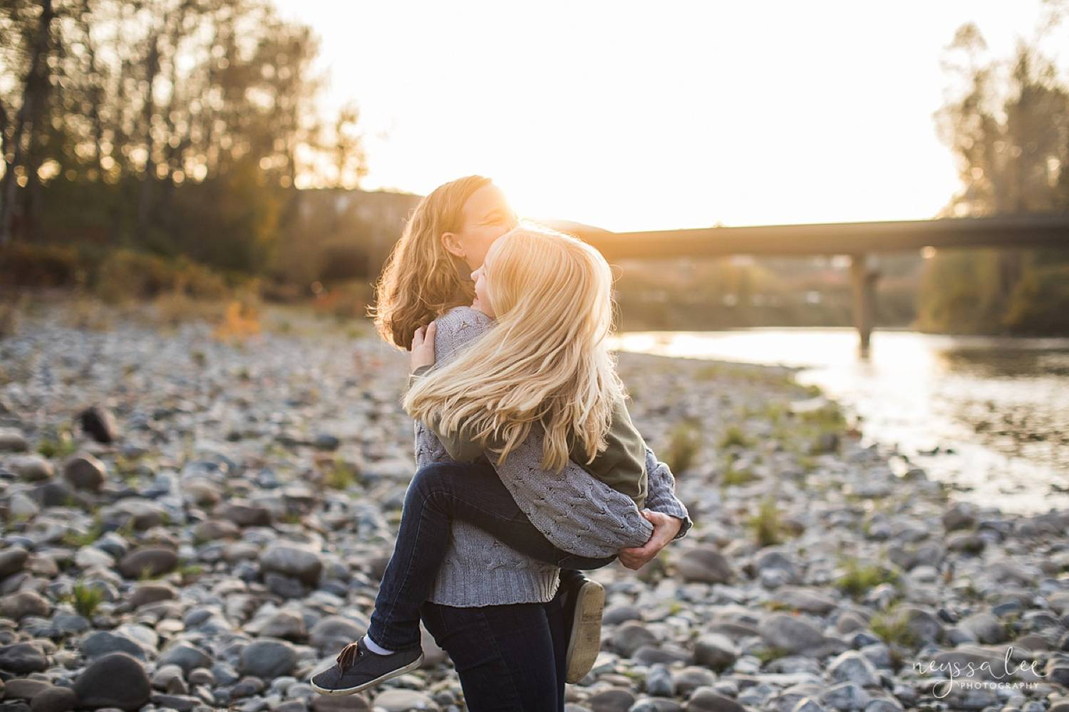 a mom spins her young daughter in her arms on a beach at sunset