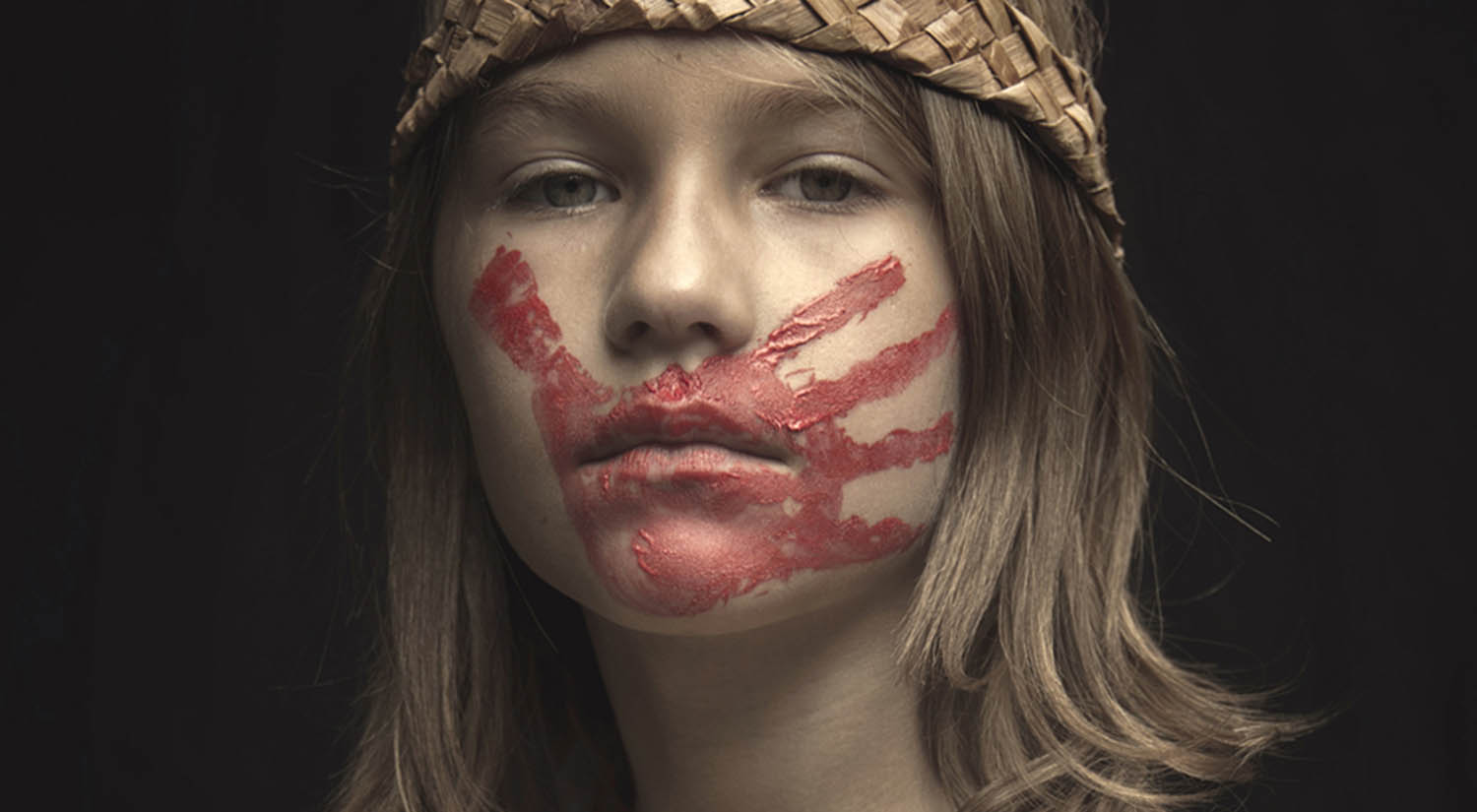 A young girl wears a red handprint across her mouth in honor of America's Missing and Murdered Indigenous Women