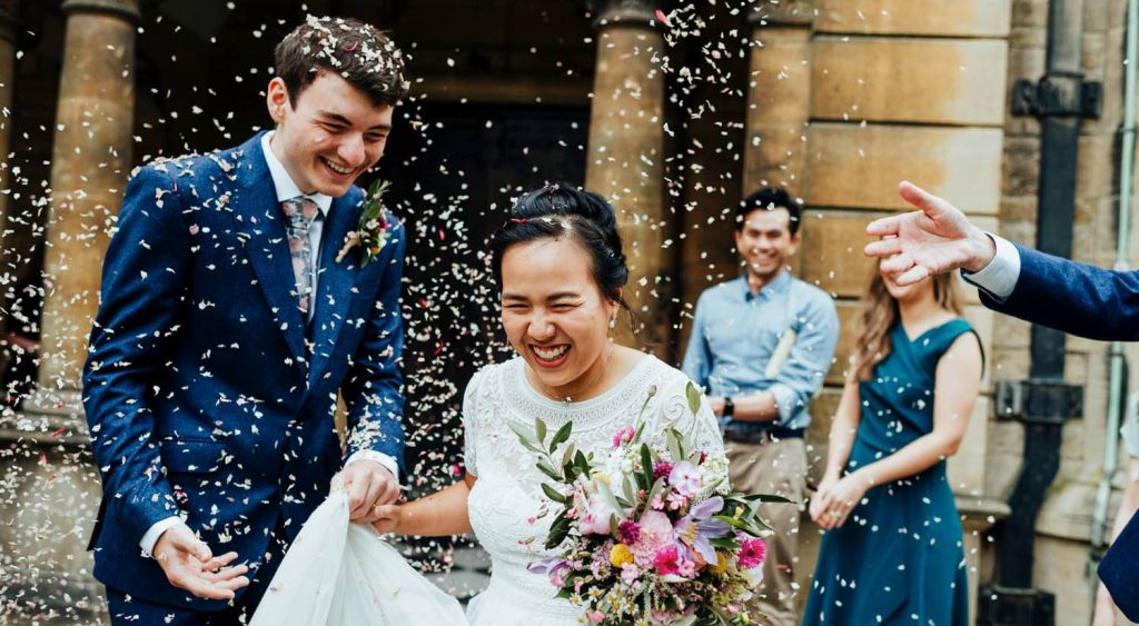 Bride and groom exit church in a shower of birdseed