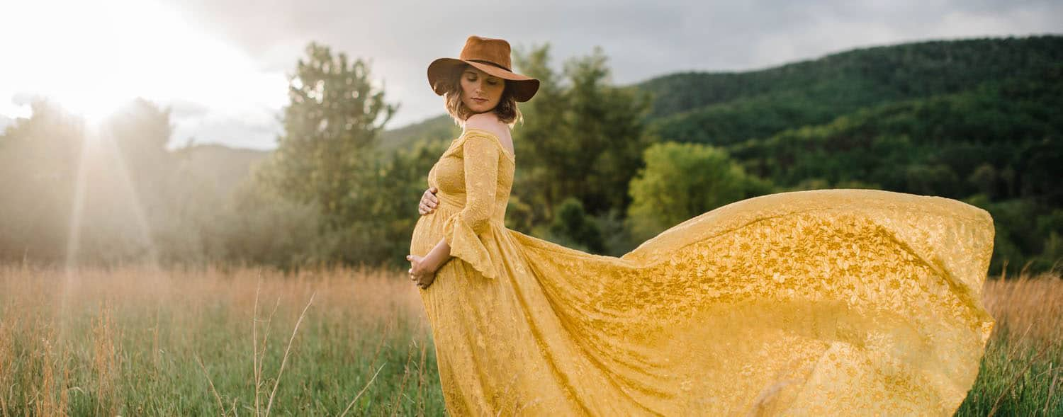 A pregnant woman stands in a field wearing a felt had and a vibrant yellow gown