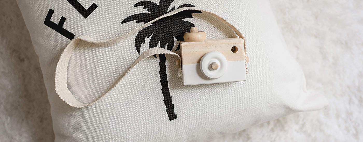 A wooden toy camera rests atop a small pillow bearing a palm tree