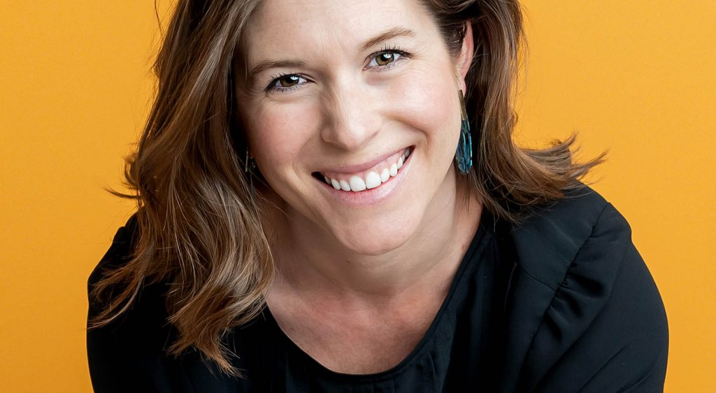 headshot of photographer Jessica Robicheaux with Bushels & Pecks photography using a gold backdrop