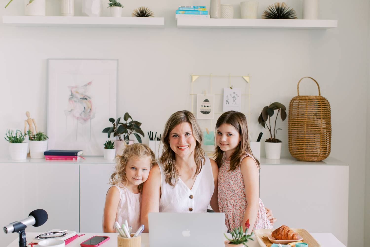 Business coach Katie Wussow sits in her clean, bright office with her daughters at her side.