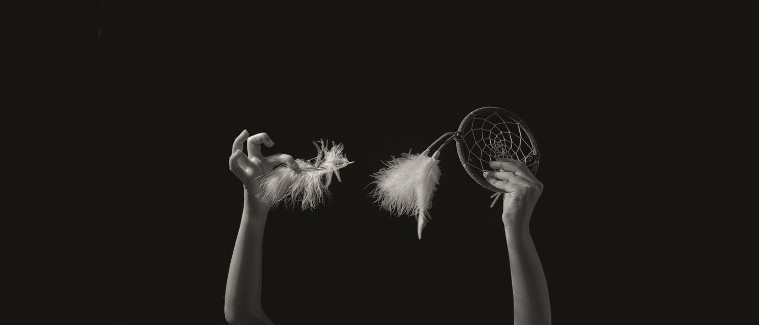 Nolan Streitberger's photograph of his daughter Haley's hands. She holds a feather in one hand and a dreamcatcher in the other.