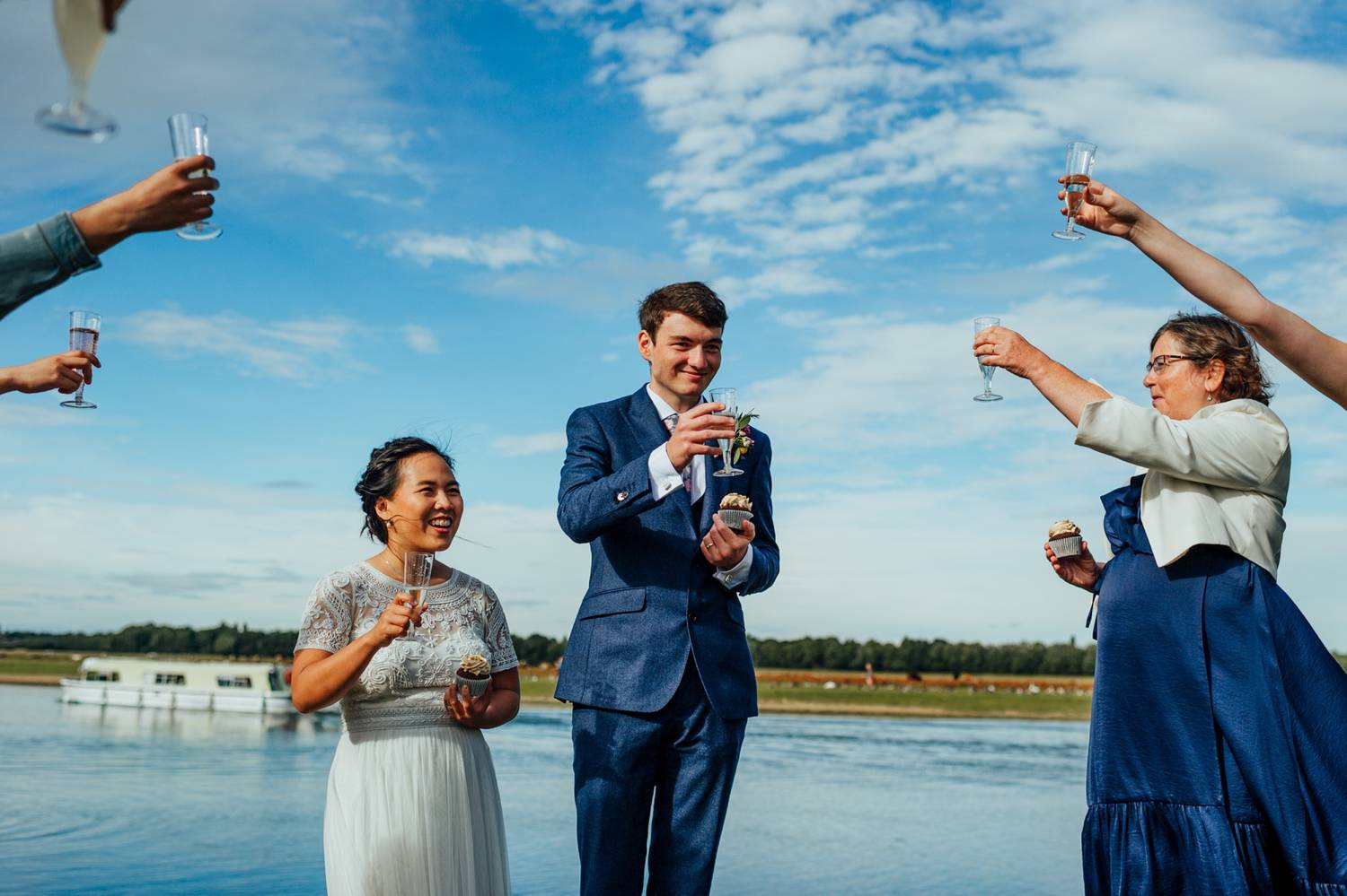 bride and groom toast by the beach