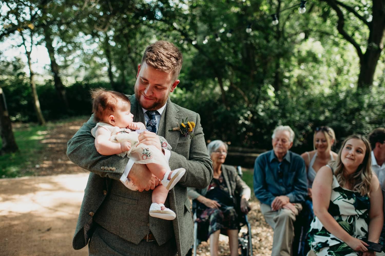 Grooms holds baby flower girl