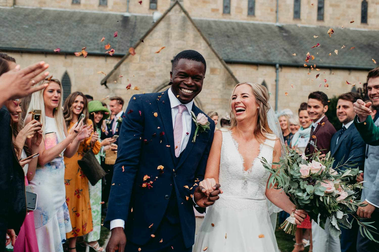 Bride and groom exit church under flower petals