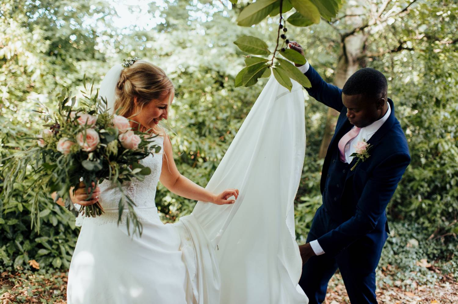 Groom helps bride with train of dress