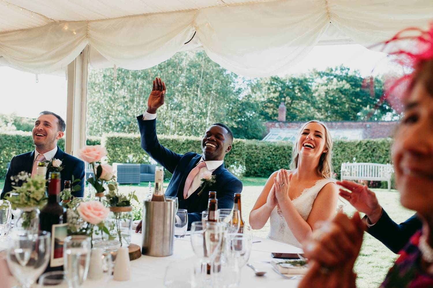 Bride and groom cheer and toast under a tent