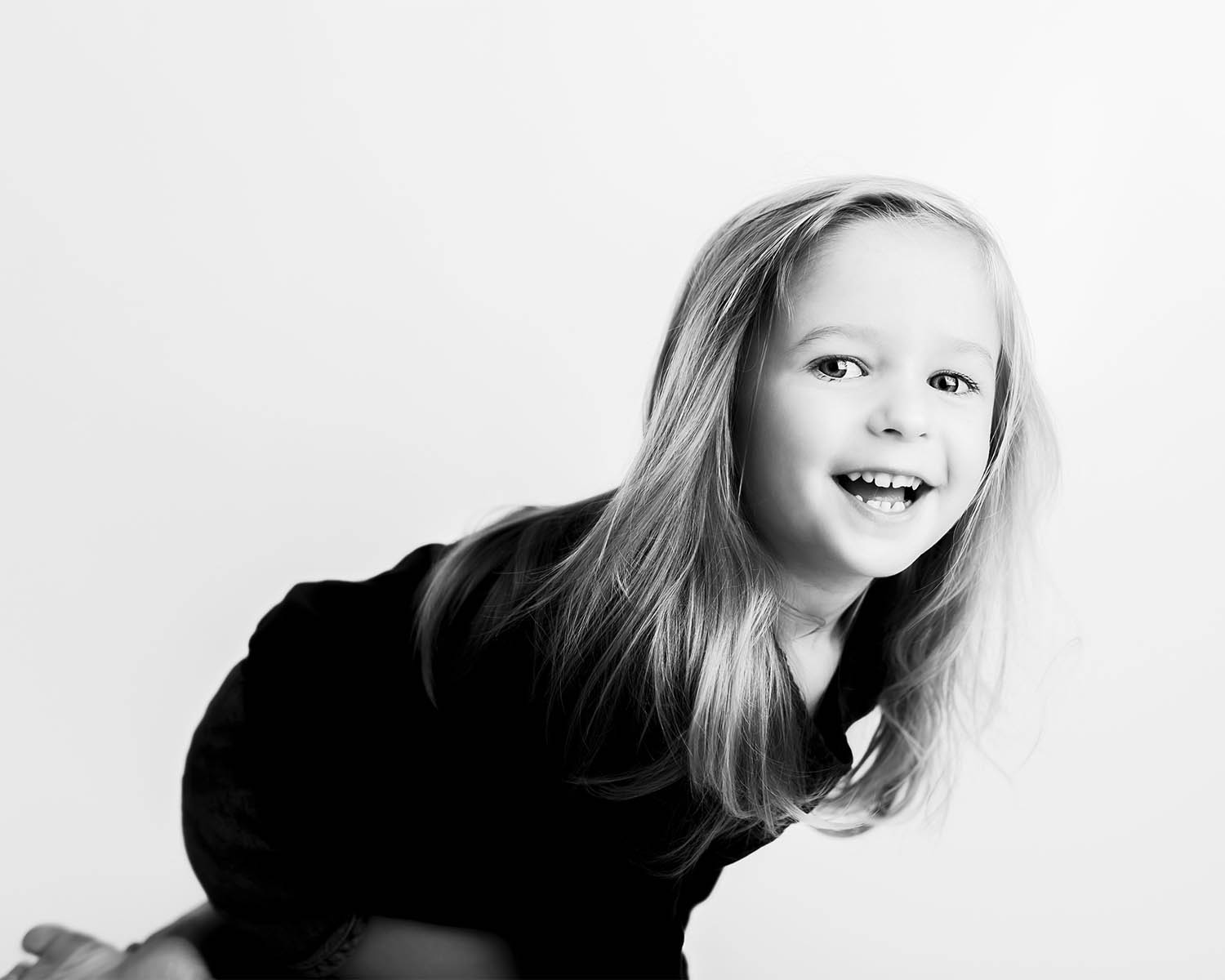 studio portrait of a little girl in black and white