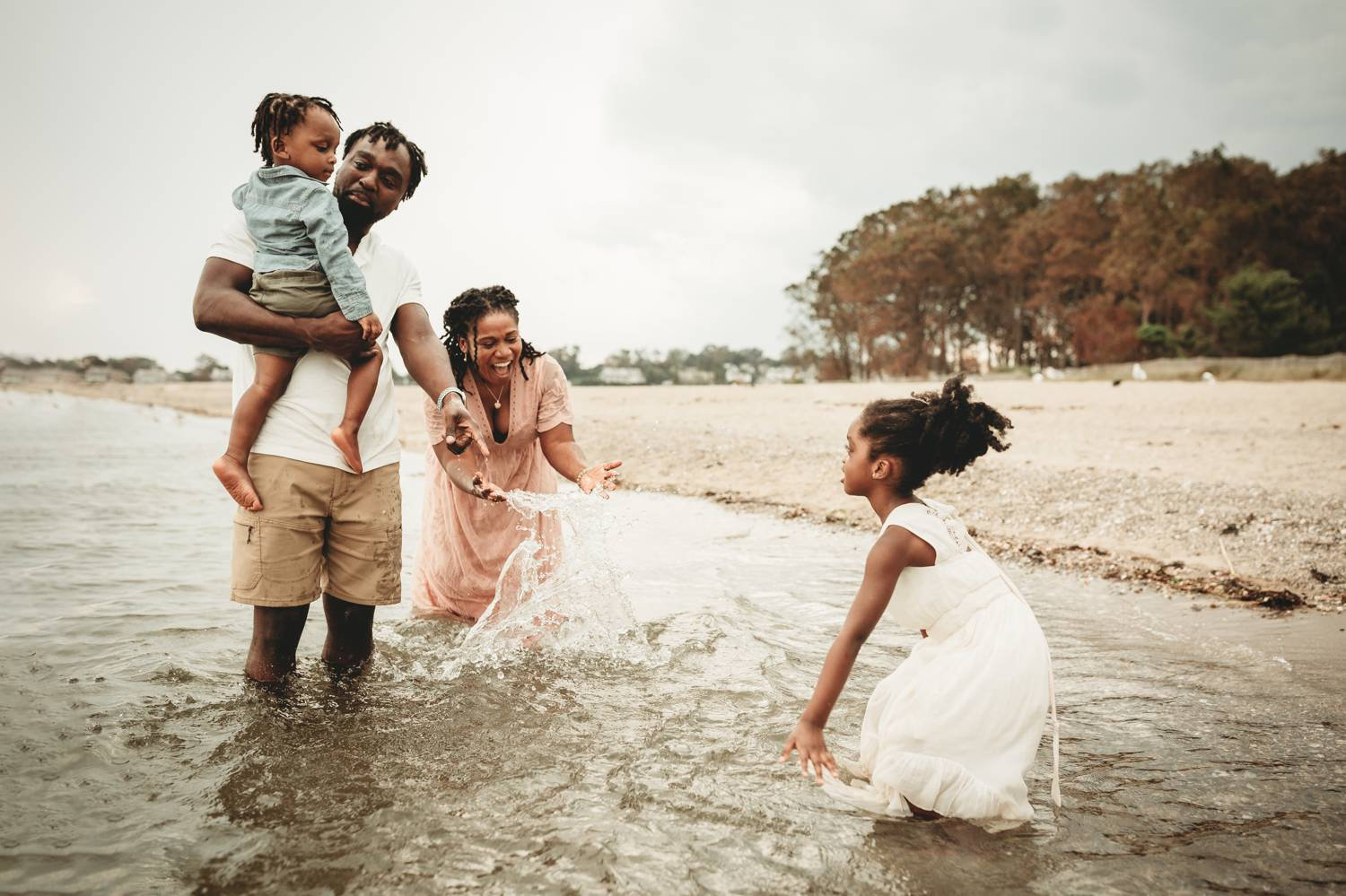 A family plays in the shallow bay waters