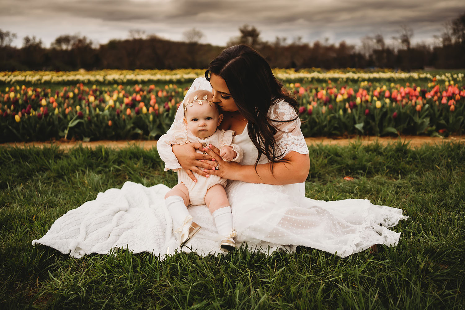 A woman in a white dress holds her baby daughter in her lap as she sits in green grass with a field of flowers behind her. Photo by Valerie Clark