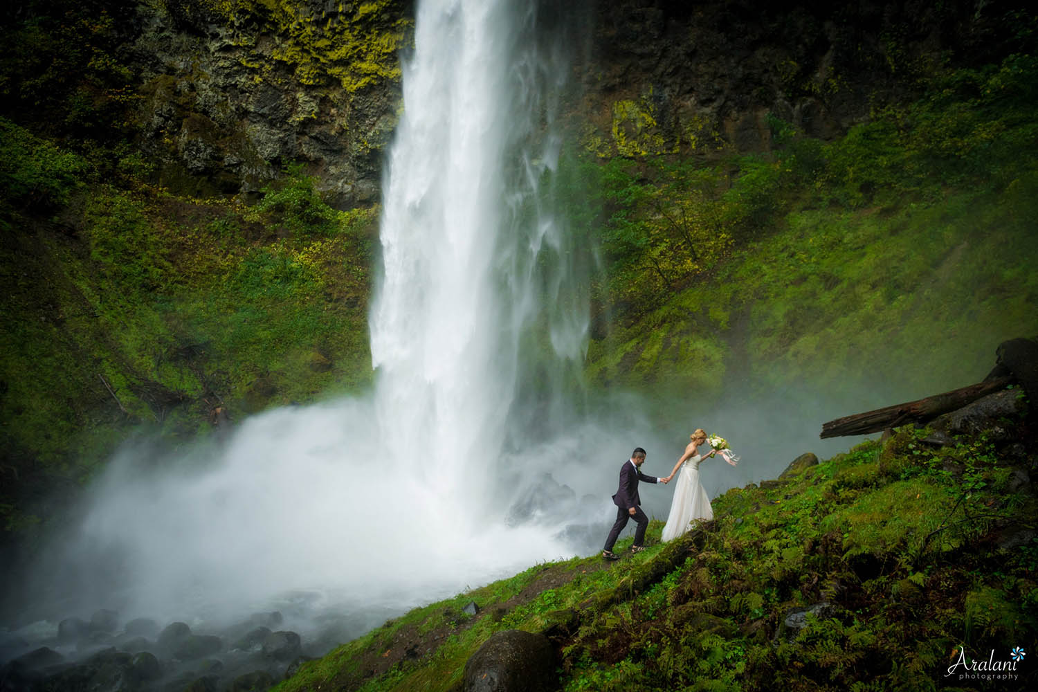 A bride and groom climb up a rocky hill as a massive waterfall pours down behind them (by Aralani Photography)