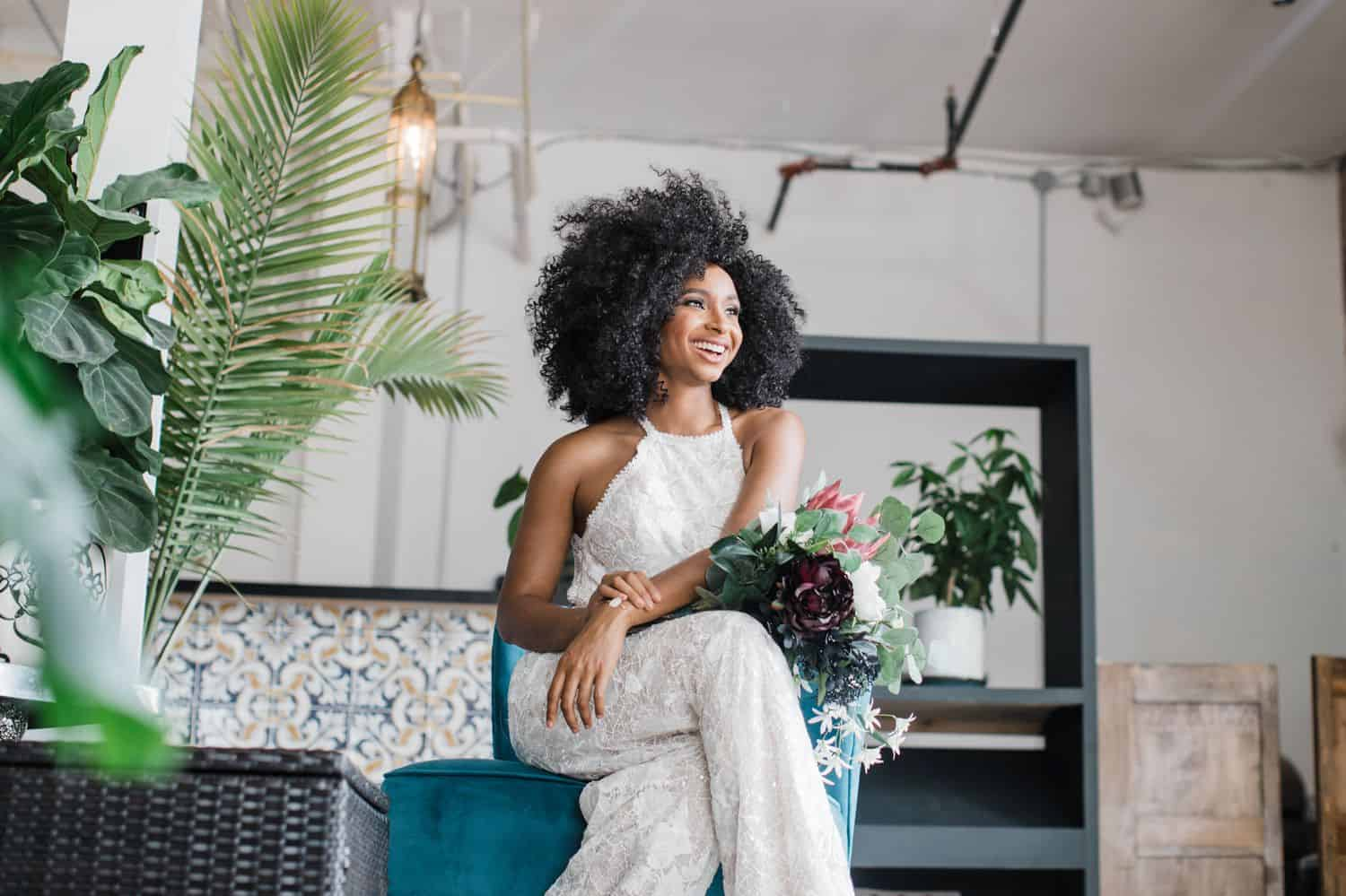 Black bride wearing a white lace jumpsuit with natural hair