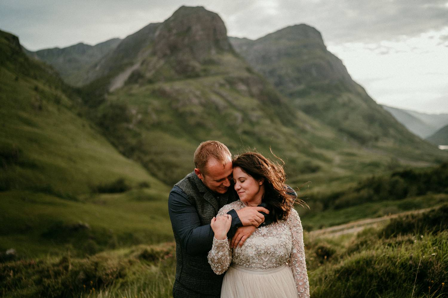 A groom stands behind his bride with his arms wrapped gently around her shoulders. She holds his arm and angles her face toward his in a loving embrace. Photographed by Rob Dight in the green hills of Ireland.