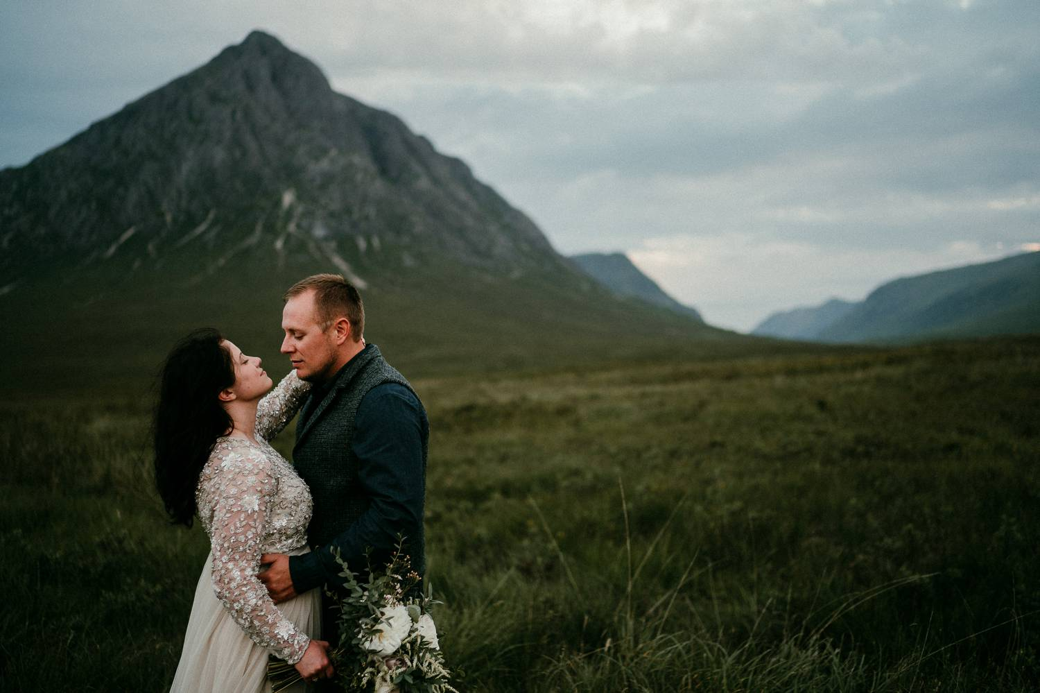 A bride and groom gaze into one another's faces in the shadow of a tall Irish mountain. Photographed by Rob Dight, who began selling photography prints to ensure his clients would always have premium quality products.