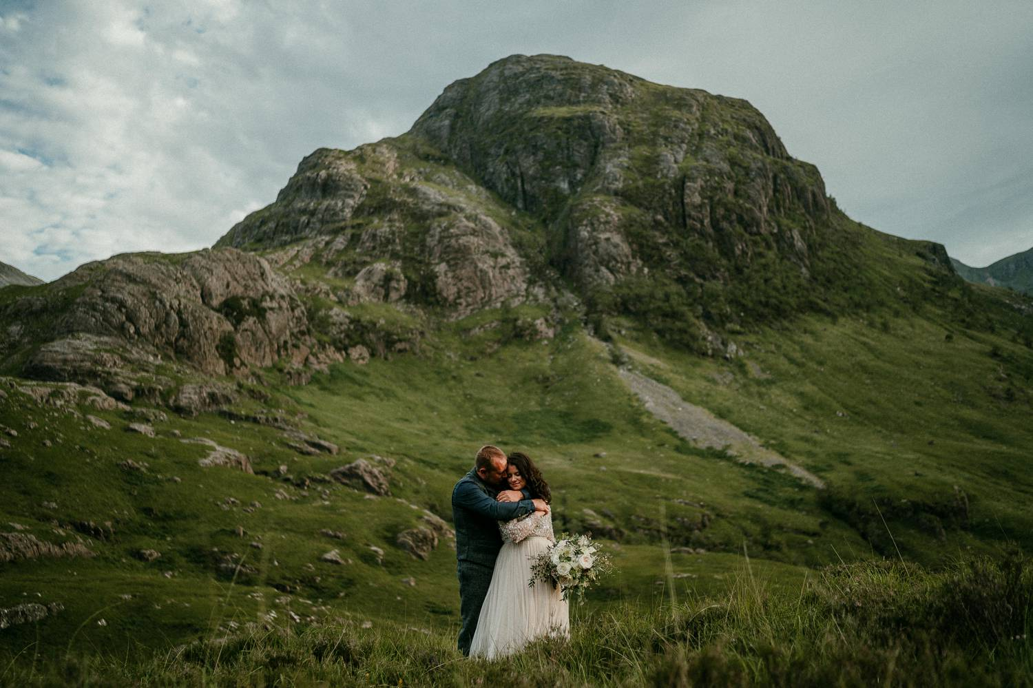 A bride and groom embrace on the wide, green hills of Ireland. Photograph by Rob Dight.