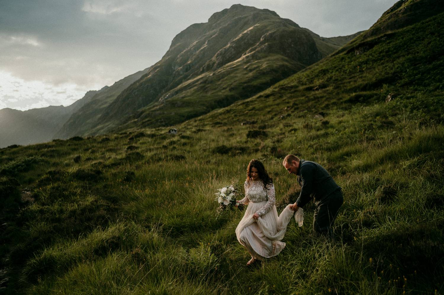 A bride walks delicately down a grassy Irish hill while her groom thoughtfully carries her train. Selling photography prints is simple when you prioritize quality over speed or cost. This image was made by Rob Dight.