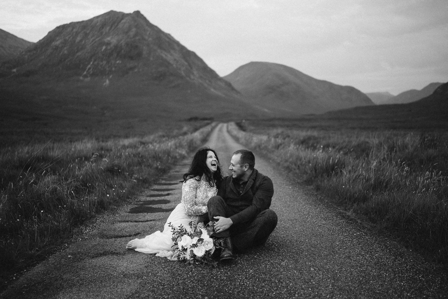 A bride and groom sit close together, laughing and embracing on an old Irish road. Black and white photograph by Rob Dight.