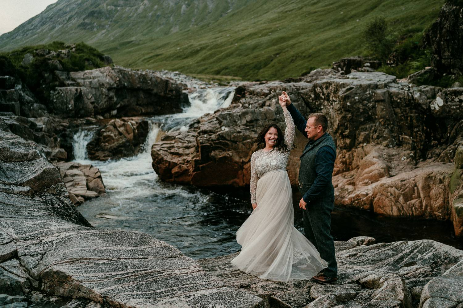 A groom spins his bride in a gentle dance move that sends her skirts twirling. They're standing beside the blue waters of an Irish creek. Photograph by Rob Dight.