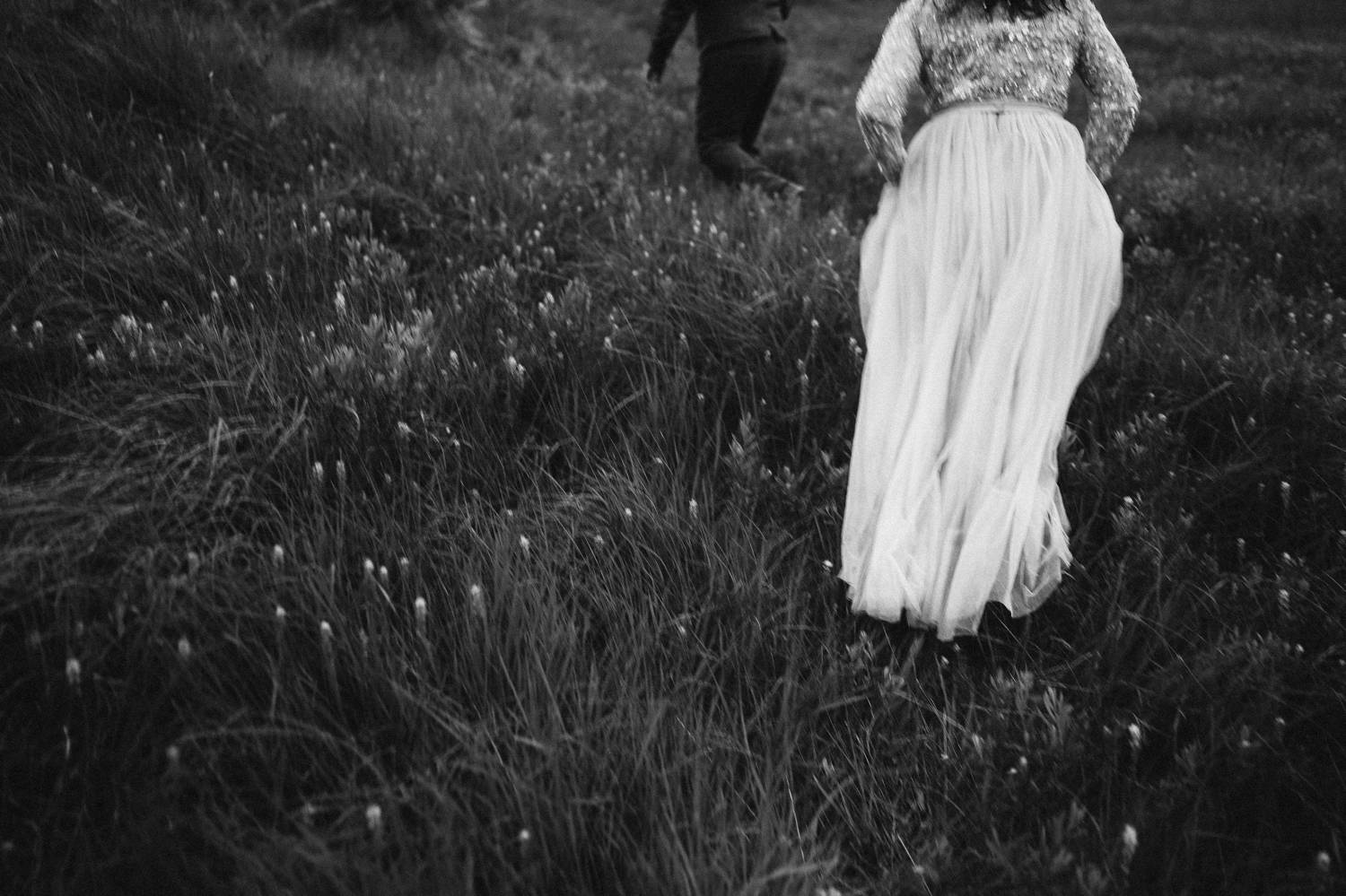 This black and white photo shows of a bride's flowing train as she climbs a grassy hill in Ireland. Photograph by Rob Dight.