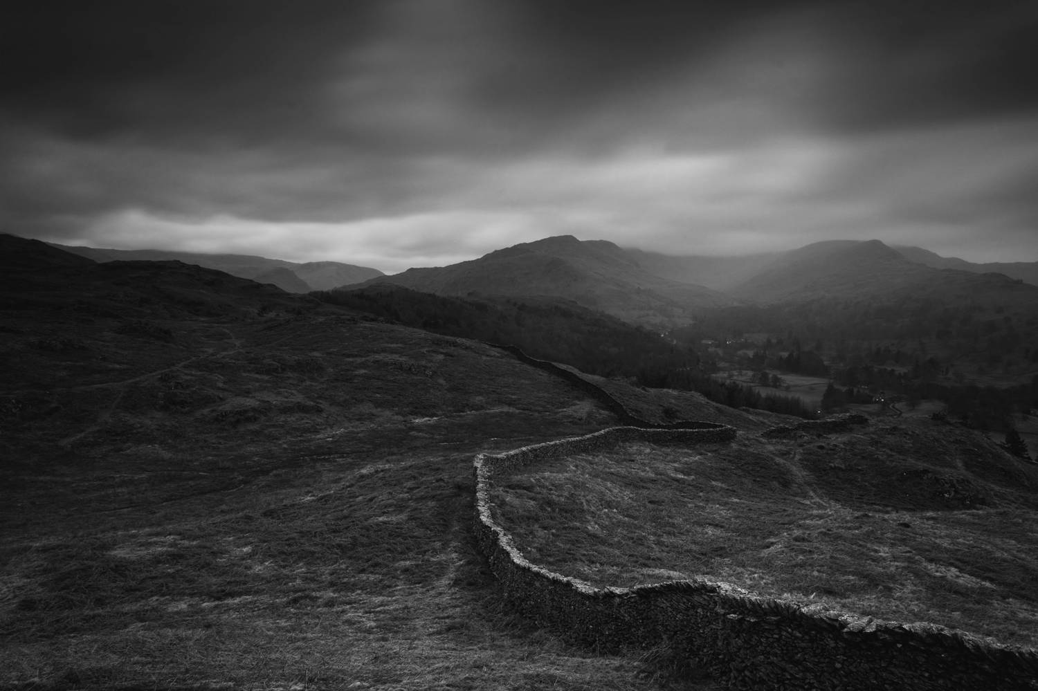 A black and white landscape photography by Joshua Wyborn depicts a grim, moody view of a low, stone farm wall in the UK.