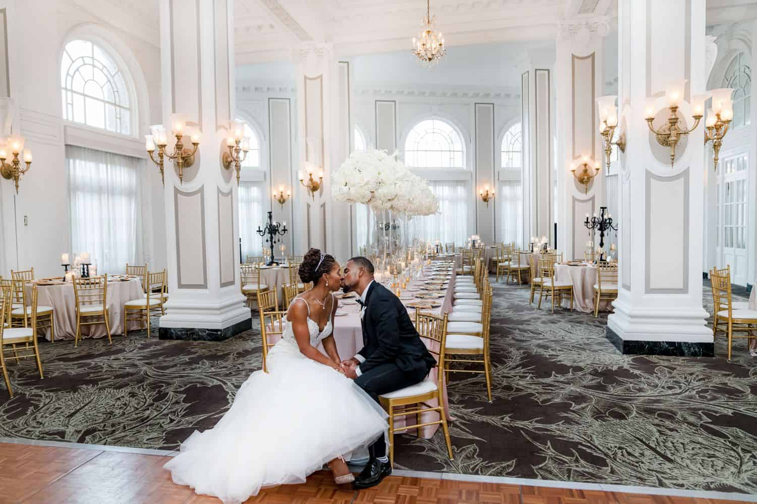 A bride in a white wedding gown kissed a groom in a black tuxedo. Both are seated in the front row of a ballroom full of chandeliers.