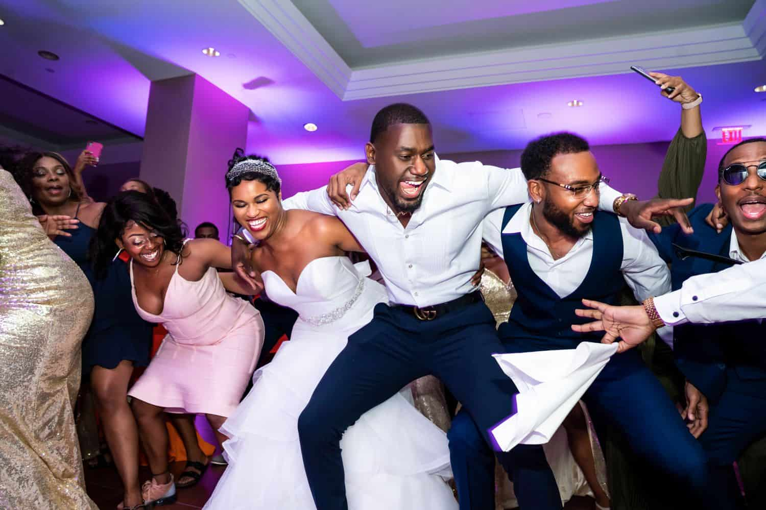 A bride and groom dance happily in a circle with their friends.