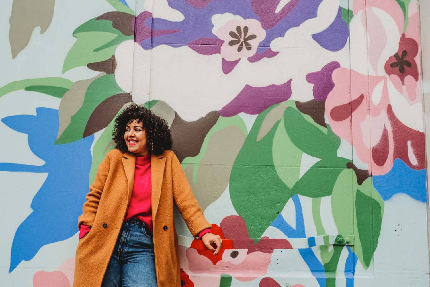 A woman business owner wearing jeans, a pink sweater, and a mustard yellow coat stands smiling against a massive wall of graffiti in Atlanta, Georgia.