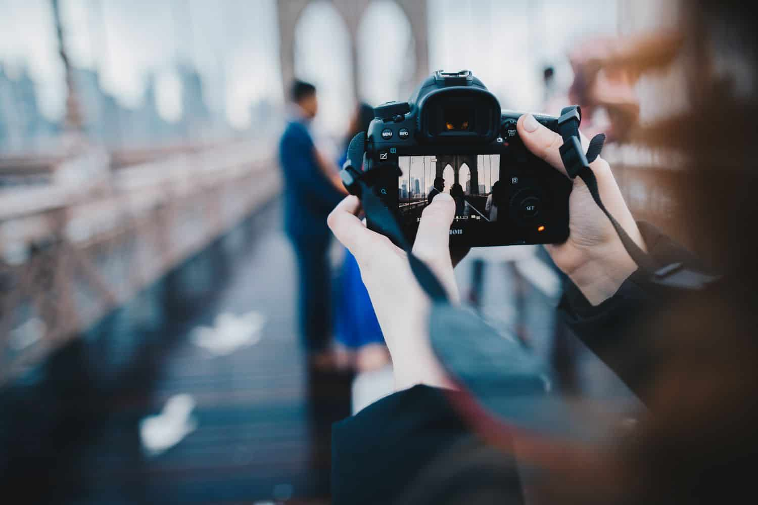 The back of a photographer's camera is in-focus as she photographs a couple standing on the Brooklyn Bridge, which is blurry in the background.