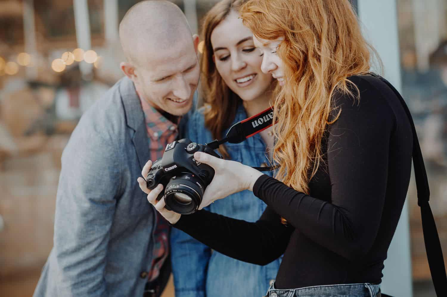 A photographer with red hair shows her camera's LCD screen to two happy clients.