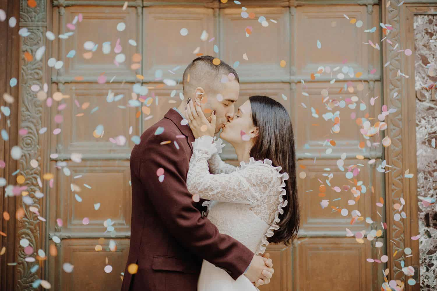 Festively dressed newlyweds kiss amid a storm of confetti.