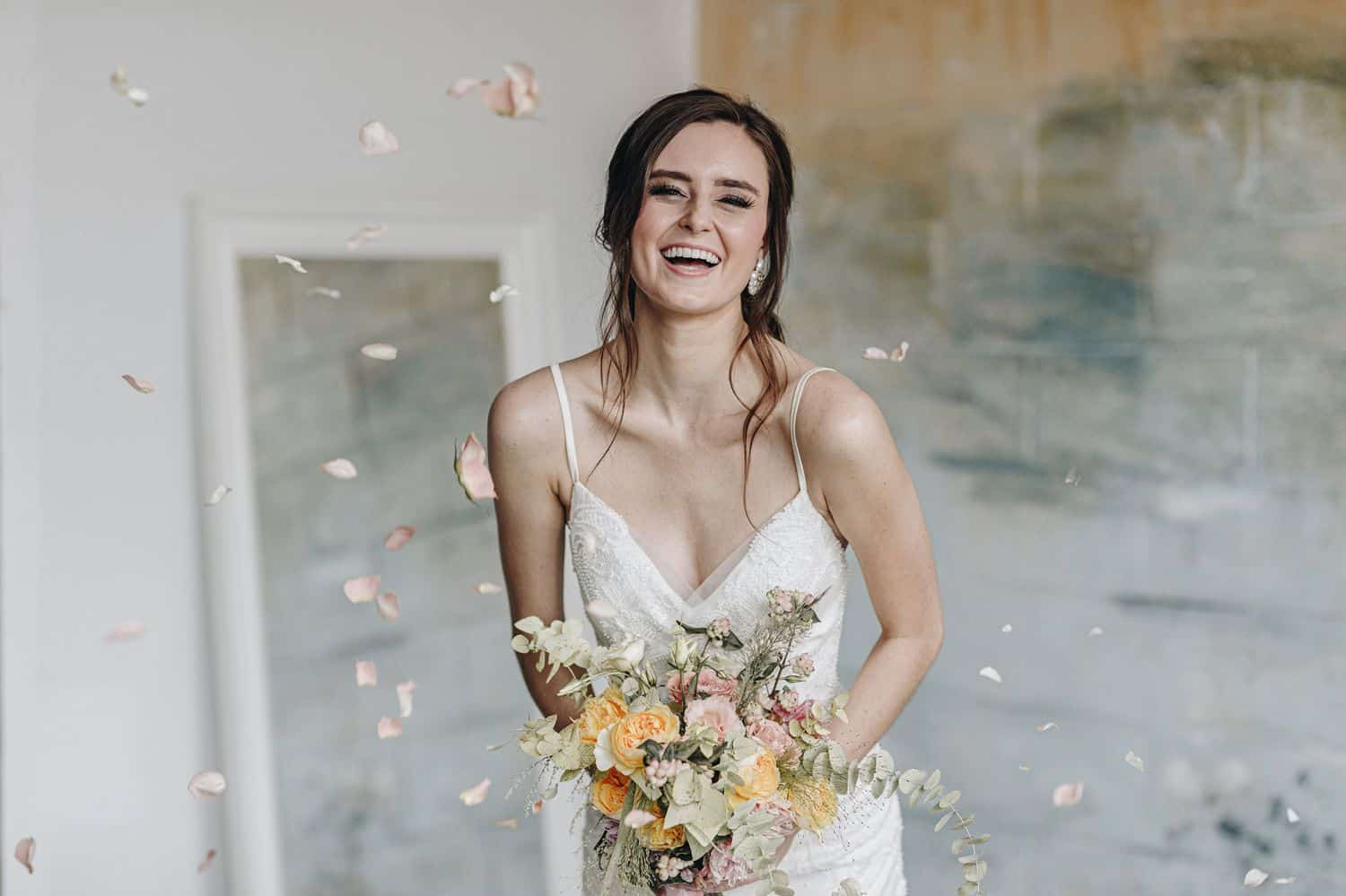 A brunette bride in a spaghetti strap wedding gown holds her bouquet and leans toward the camera laughing.