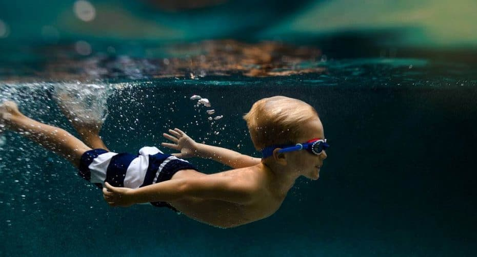 A child wearing striped swim trunks and goggles is swimming underwater with his arms stretched behind him
