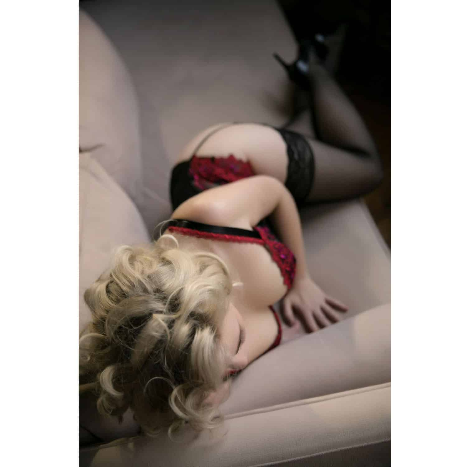 OWN Boudoir's color portrait of a woman in red lingerie lying on a sofa