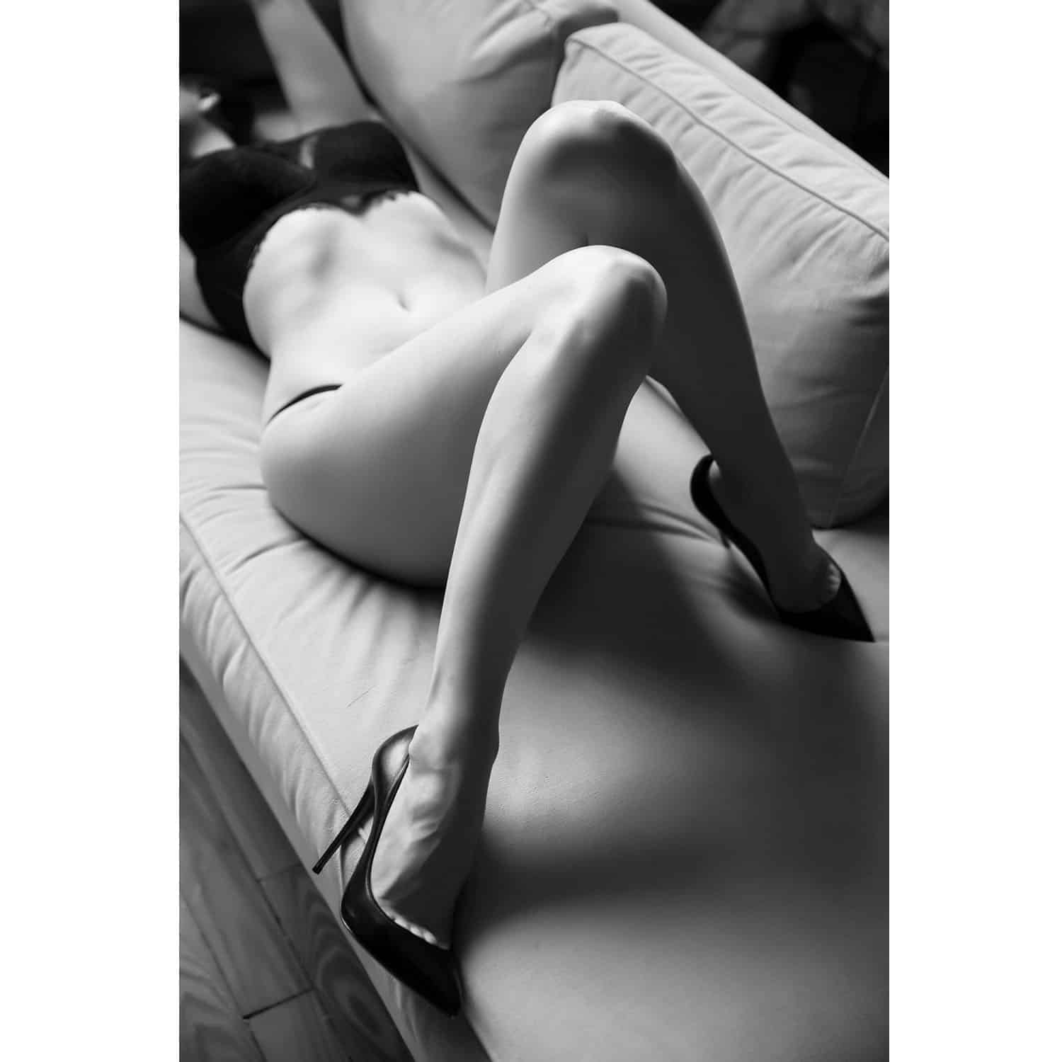 OWN Boudoir's black and white portrait of a woman in lingerie and stiletto heels lying on her back on a sofa