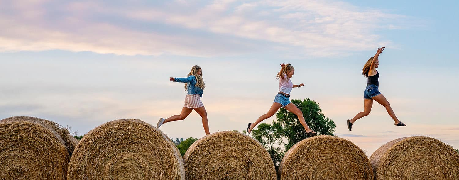 Three senior girls leap across bales of hay at sunset