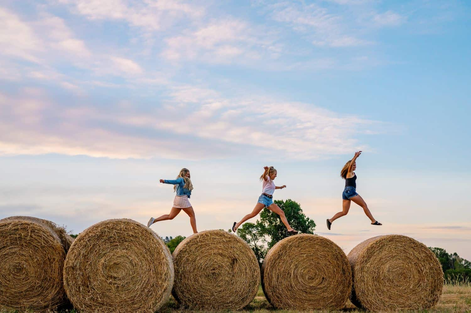 Three senior girls leap across hay bales at sunset
