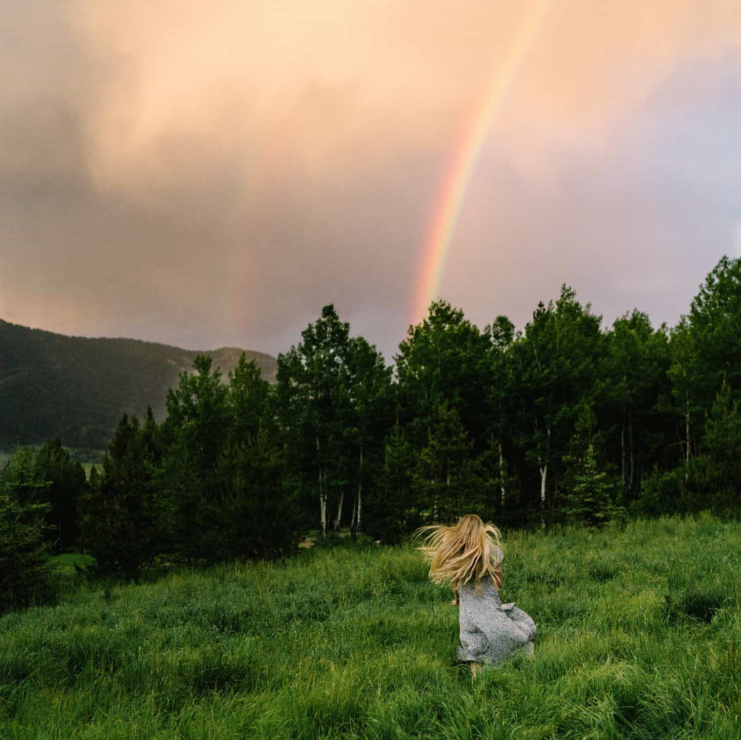 A senior girls runs through a lush green field toward a rainbow in a gloomy sky