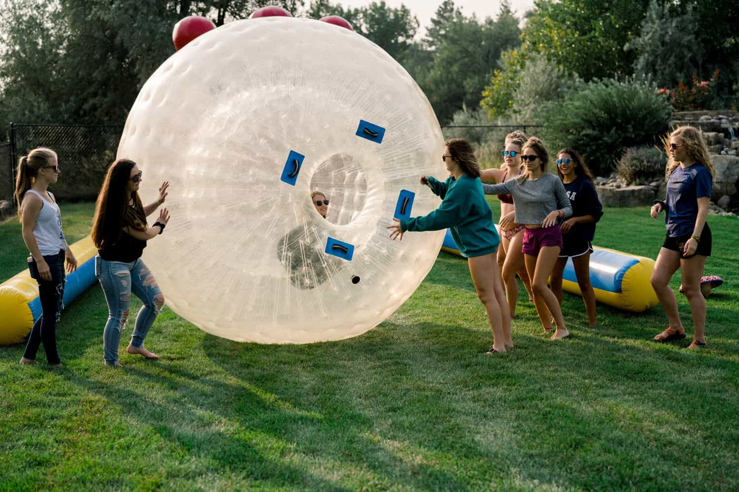 A group of senior girls play with a gigantic hamster ball in a newly-cut field of grass