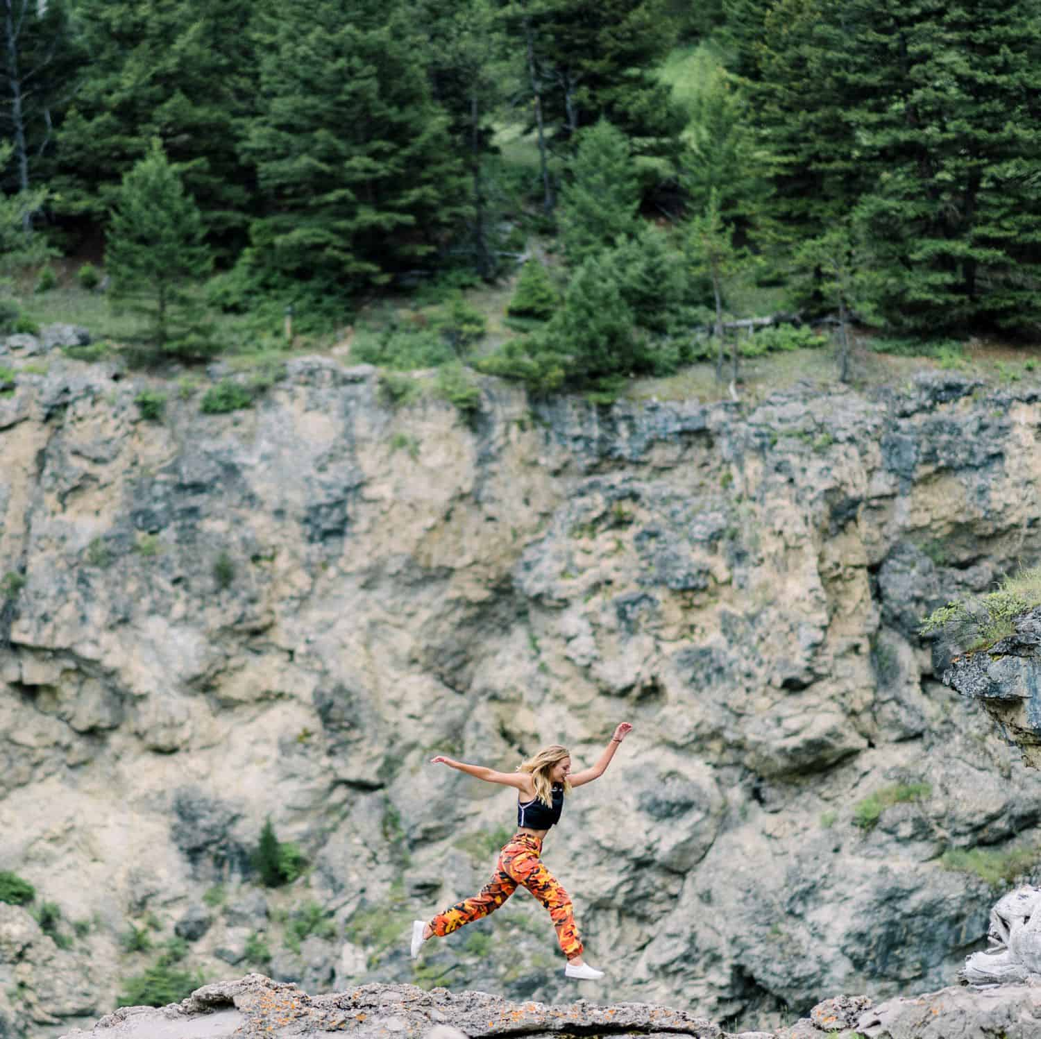 A senior girl leaps across rocks along the side of a cliff