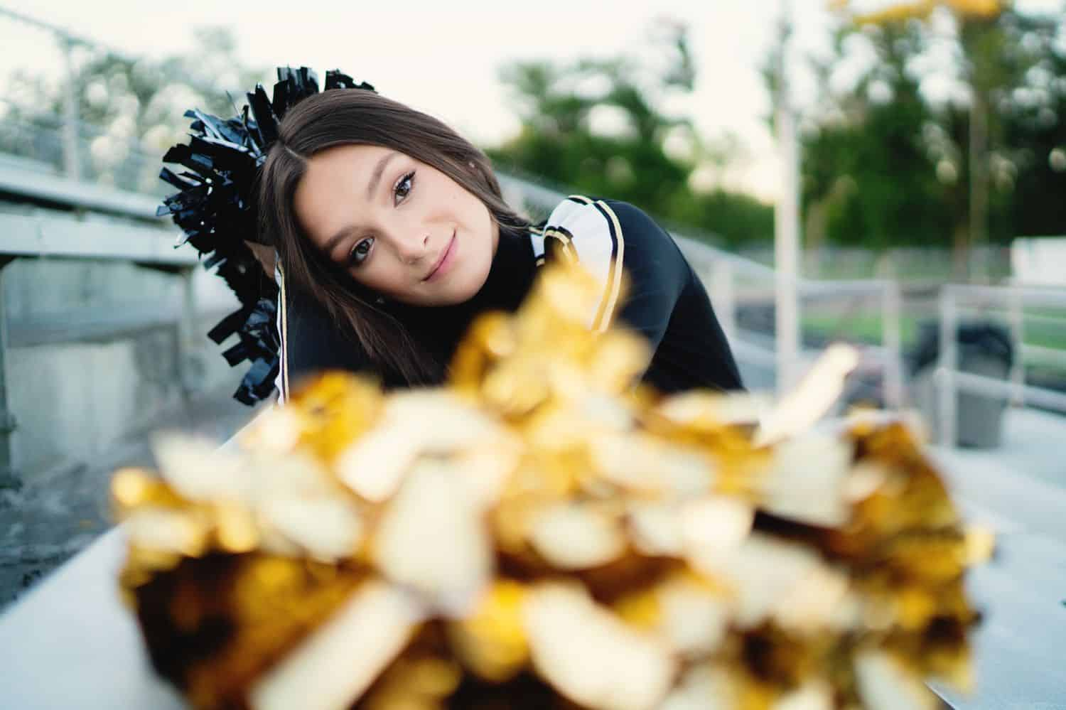 A senior girl sits beside a football field with her cheerleader pom-poms